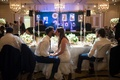 a newlywed couple sitting in ghost chairs at head table share a kiss