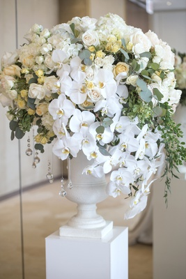 floral arrangement on pedestal with white orchids, small yellow roses, ivory roses, eucalyptus