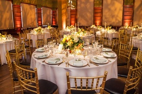 Wedding reception gold black chairs gold room museum wedding low centerpiece yellow flowers candles