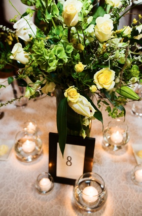 tabletop with yellow and green centerpiece and floating candles
