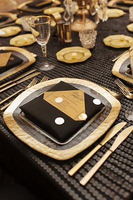 gold-rimmed hammered charger, black napkins, kite set gold menu, white polka dots