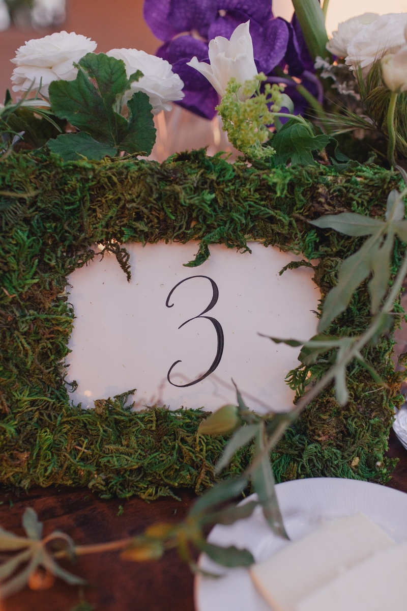 White and black table number in grass frame