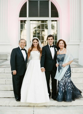 Mother of groom in strapless evening gown Carolina Herrera with shawl and necklace father of groom