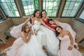 brie and bridesmaids in morilee pose draped over each other at windo seat