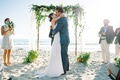 first kiss ceremony beach pacific ocean wood arch verdure sand oceanside california wedding