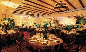Ballroom with wood beamed ceilings and lush flower arrangements