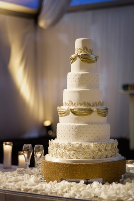 White wedding cake with golden ribbons, pearls, and gold-rimmed sugar roses