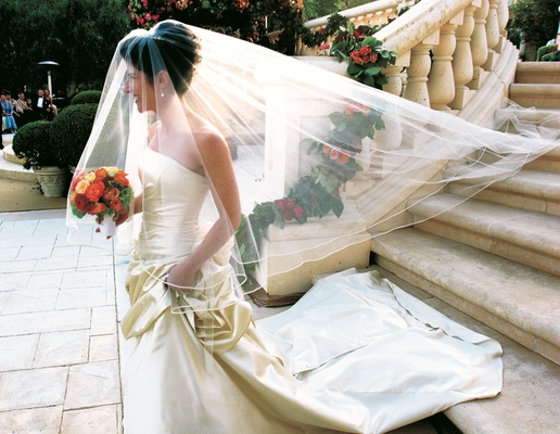 Bride in a strapless, cream colored wedding gown carries