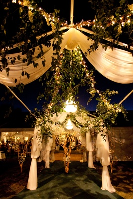 Garlands of greenery and white fabric arch