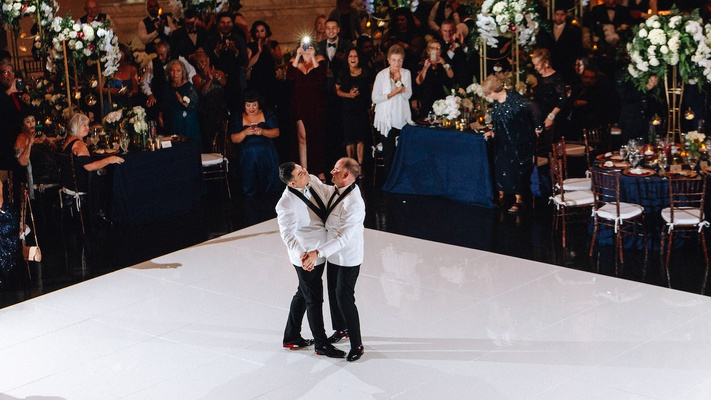 same-sex wedding gay couple, grooms sharing their first dance wearing white jackets