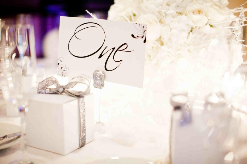 Favor box wrapped in silver ribbon on guest table