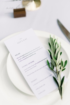 "white china with ""let's eat"" menu and olive branch on top"