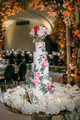 5-tier wedding cake with pink flower and greenery on bed of white flowers