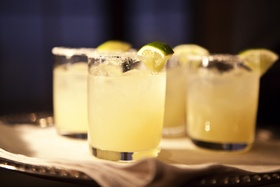 Short glass cups of margarita with salt and lime