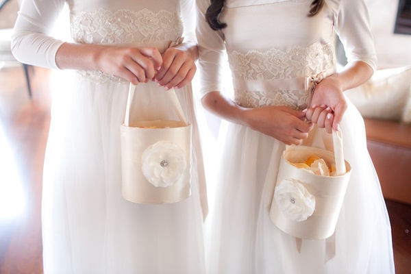Flower girls holding unique basket filled with peach petals