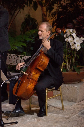 cellist performing at nighttime wedding ceremony