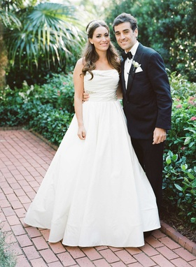 Bride in strapless Reem Acra wedding dress hair down with headpiece and groom in tuxedo bow tie