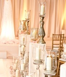 candles in metallic stands and vessels line the wedding aisle