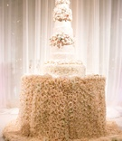 Tall white wedding cake with sugar flower tiers on top of blush pink rose tablecloth table design