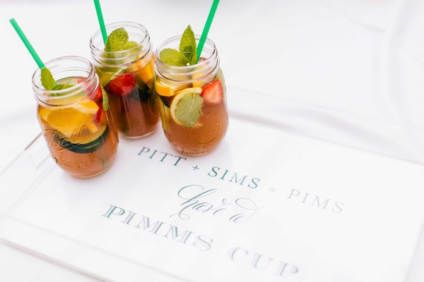 Wedding signature cocktail pimms cup with fresh fruit and mint green straws on lucite tray