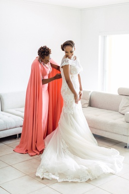 maid of honor in purple lagos coral dress with cape helps bride in lace dress