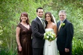 Bride in a Claire Pettibone gown, groom in pinstripe suit and light green tie, and family