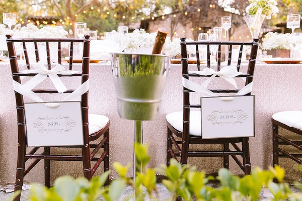 Head table with gold sequined tablecloth and Mr. and Mrs. signs hung from ribbon, outdoor reception