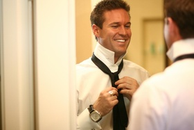 Man putting on tie for wedding day