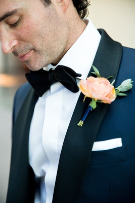 Light orange flower boutonneire on groom's navy blue tuxedo black bow tie