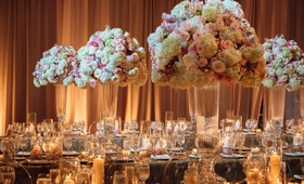 Wedding reception with tall flower arrangements glass crystal vases gold linens candles drapery