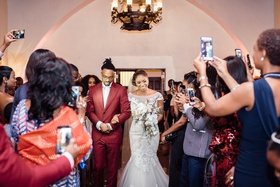 bride walked down the aisle by her brother, guests take pictures of processional
