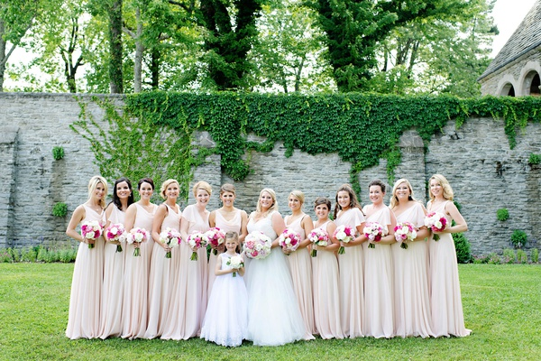 bride with twelve bridesmaids in blush dresses mismatched necklines sleeves white flower girl dress