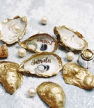 Gold painted oyster shells with calligraphy names and mens wedding band, engagement ring, diamond