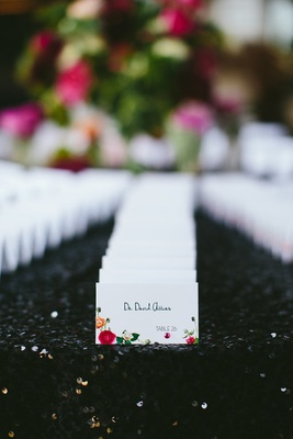 escort cards with flower print on black sequin linen