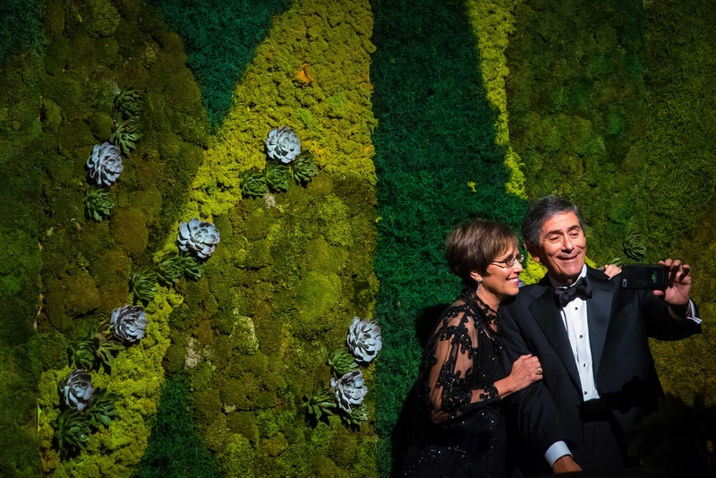 Adult wedding guests in black tie attire taking selfie photo in front of moss succulent wall