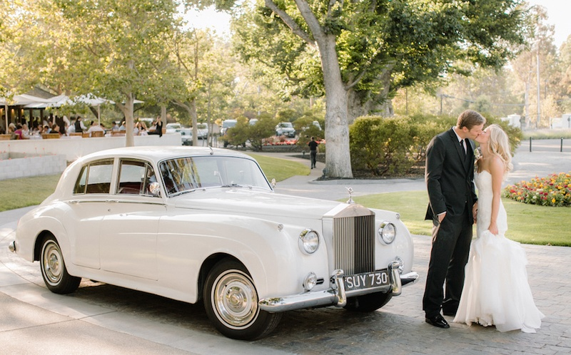 Bride in a strapless Hayley Paige dress kisses groom in black tuxedo by vintage white Rolls-Royce