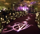 Wedding ceremony aisle with dark purple carpet, projected monogram, and candles in crystal vessels