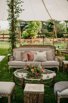 wedding reception upholstered stool coffee table pink orange yellow flowers settee sofa dusty rose