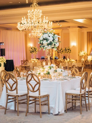 square table with oval back gold chairs candles white hydrangea tulip centerpiece lower florals gold