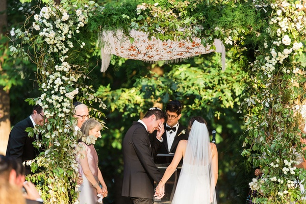 Wedding ceremony greenery woods area with groom touching eyes parents on both sides Jewish ceremony
