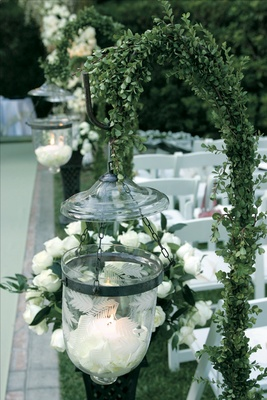 Glass vessel filled with white rose petals and candle hangs from a hook covered in greenery