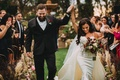 Stephanie Perez and Brandon Hampton walking up aisle bride in detachable train overskirt