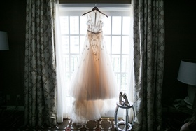 Monique Lhuillier wedding dress on hanger with shoes on stool