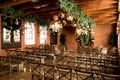 Wood beams brick wall urban chic wedding ceremony venue chandelier greenery vineyard chairs benches
