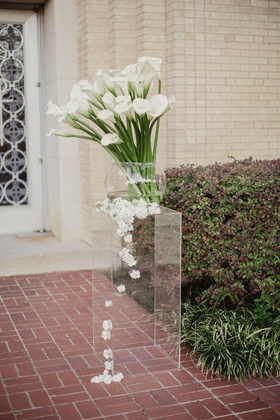 calla lilies on long stems in glass bowl, white blossoms cascade down lucite stand