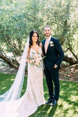 bride in calla blanche wedding dress pastel bouquet cathedral veil groom in pink tie pocket square