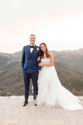 Bride in Monique Lhuillier wedding dress horsehair hem strapless holding groom's arm navy blue suit