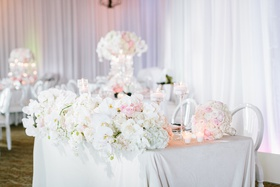 sweetheart table with white linen, front of table lined with lush display of orchids and ivory roses