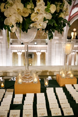 wedding reception escort card table tall arrangement white orchid rose greenery gold escort cards