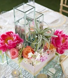 Centerpiece composed of square vases with pink and orange flowers, succulent, and floating candles